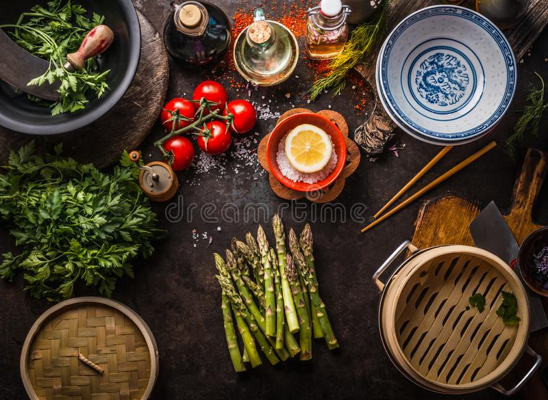 Green asparagus bunch , asian bamboo steamer and fresh tasty ingredients for healthy vegetarian eating and cooking in asian style. On rustic table with stock photos