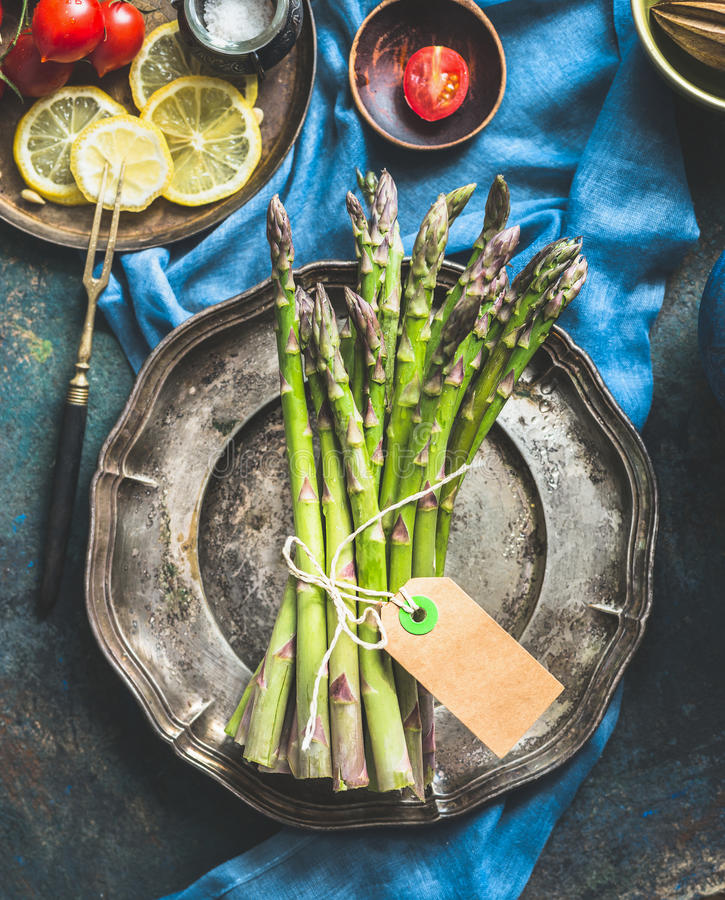Green asparagus bunch with brown string and blank tag on vintage metal plate. stock photography