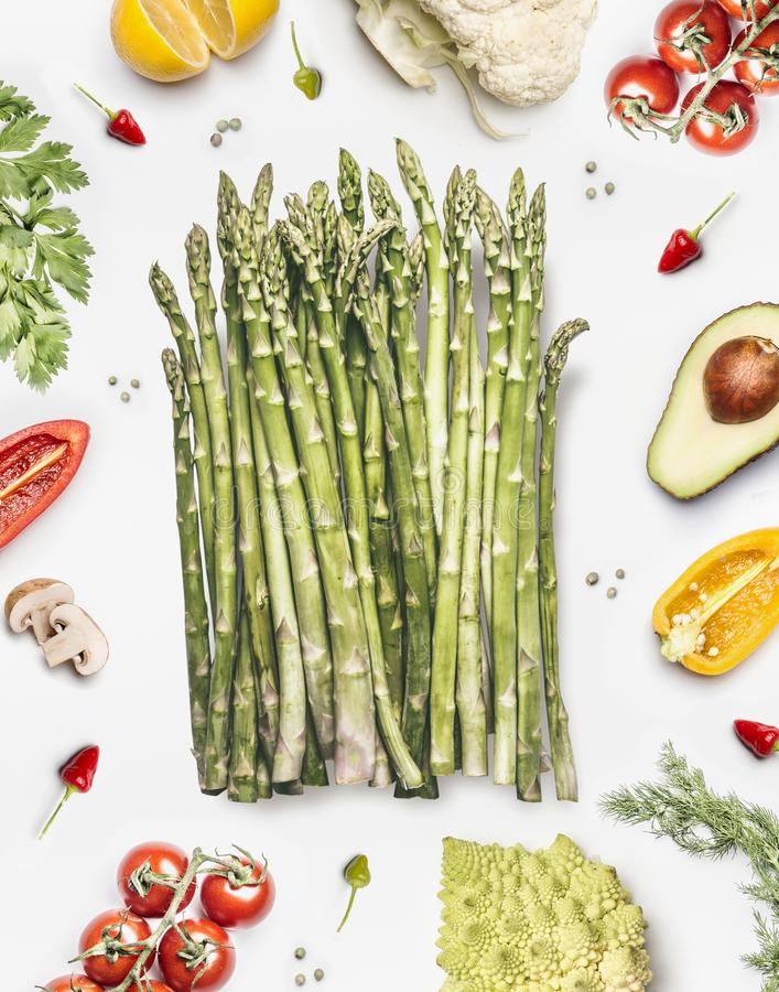 Green asparagus bunch with vegetables ingredients on white background, top view, flat lay. stock photography