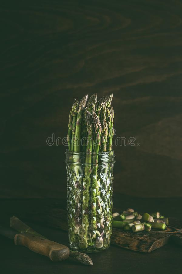 Green asparagus in glass jar with water on table at dark background. Fresh asparagus storage. Spring seasonal vegetables. Green asparagus in glass jar with water royalty free stock photos