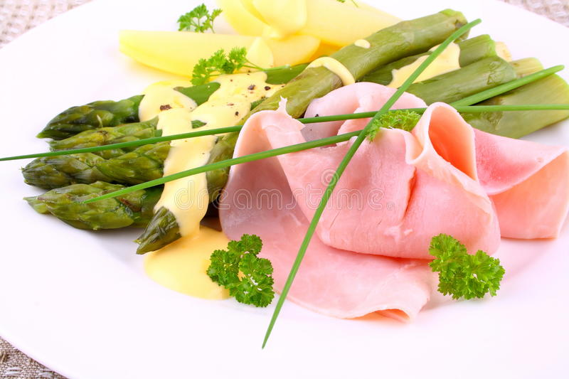 Green asparagus with prosciutto, potato, chives and sauce stock images