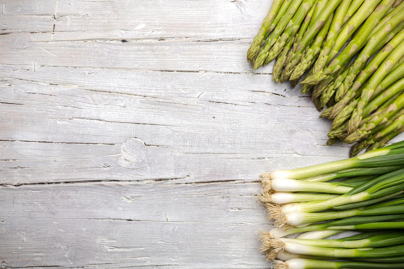 Green asparagus and spring onions on white wooden background royalty free stock photography