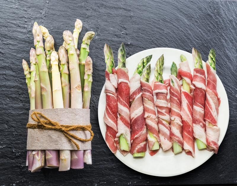 Green asparagus sprouts wrapped in ham on graphite background. Top view stock photo