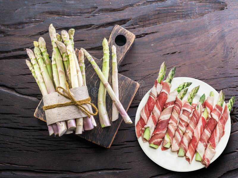 Green asparagus sprouts wrapped in ham on wooden table. Top view stock image