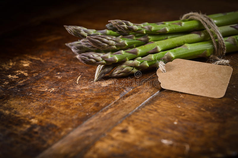 Green asparagus tips and blank tag. Selective focus close up view of green asparagus tips wrapped at stem with brown string and blank tag with copy space over royalty free stock photos