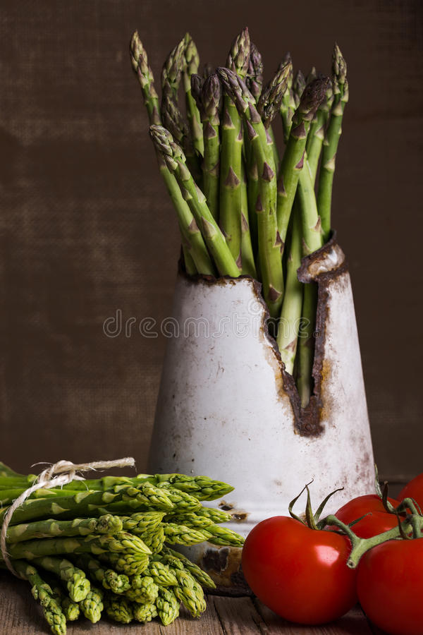 Green asparagus with tomatoes on brown background royalty free stock images