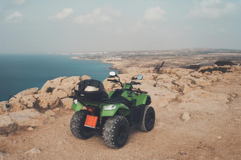 Green ATV offroad on sea and sky background. Cyprus Ayia NAPA. quad bike for rent for entertainment of tourists. Off-road driving. Green ATV offroad on sea and royalty free stock image