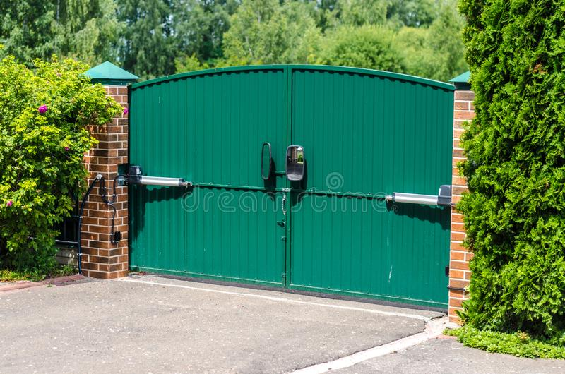 Automatic electric gates in a private house. Green automatic electric gates in a private house stock images