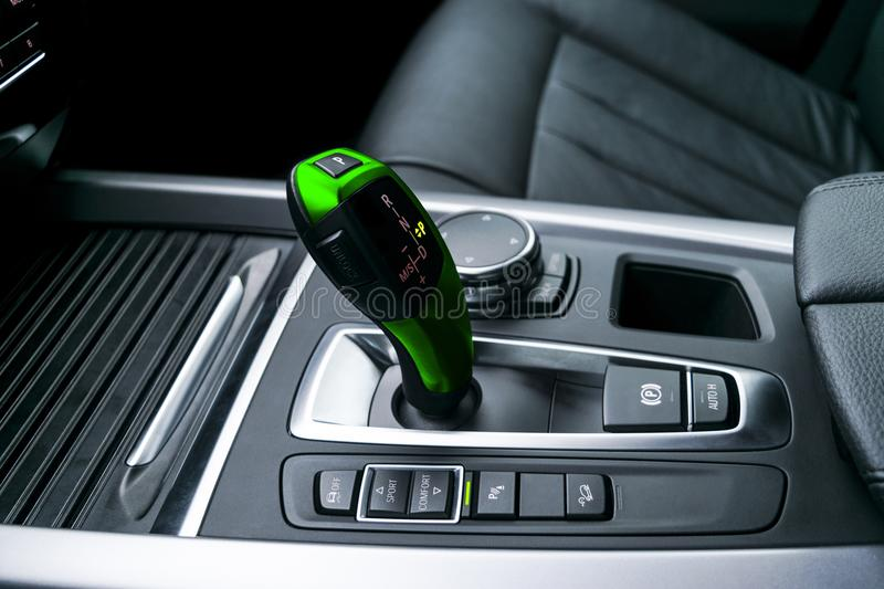 Green Automatic gear stick transmission of a modern car, multimedia and navigation control buttons. Car interior details. Transmission shift royalty free stock photography