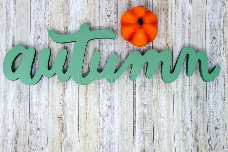 Green Autumn text phrase with orange pumpkin on wood background. Green Autumn text phrase with four decorative plaid pumpkins. Useful for fall banners and royalty free stock photography