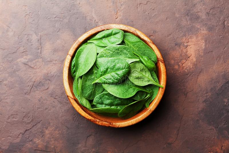Green baby spinach leaves in wooden bowl on rustic stone table top view. Organic healthy food. stock image