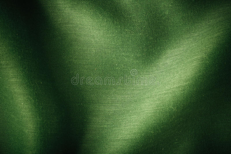 Green background abstract cloth wavy folds of textile texture. Wallpaper design of elegant material royalty free stock photo