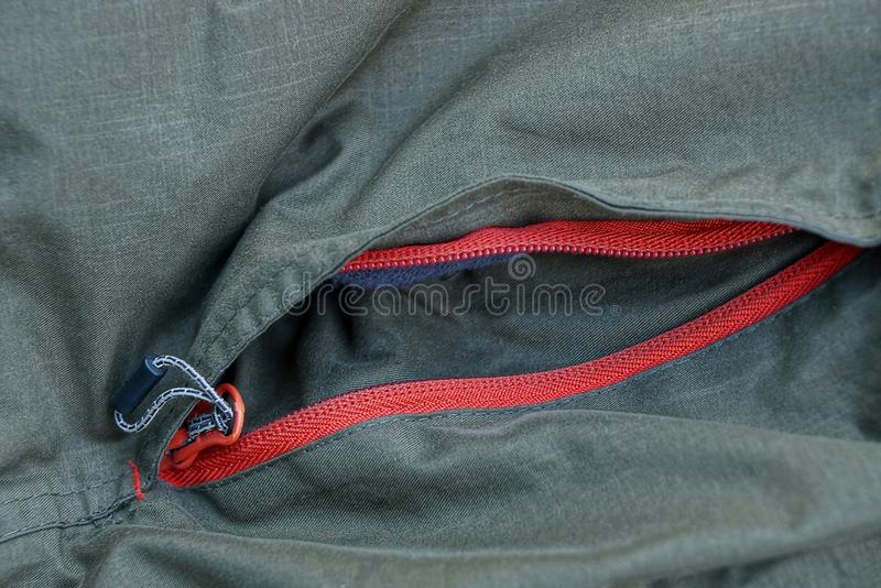 Green texture with a pocket and a red clasp. Green background of cloth with a pocket and a red clasp stock photos