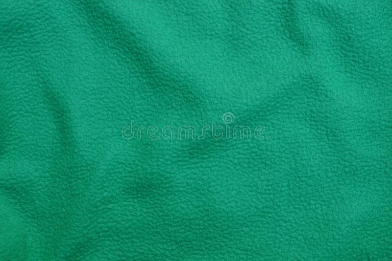 Green fabric texture of crumpled fabric on clothes. Green background of crumpled fabric on clothes stock photos