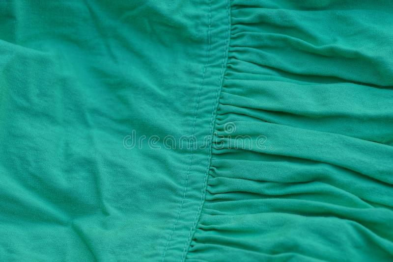 Green fabric texture of crumpled fabric on clothes. Green background of crumpled fabric on clothes royalty free stock photos