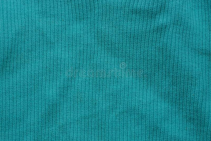 Green fabric texture from a piece of crumpled clothes. Green background of fabric from a piece of crumpled clothes royalty free stock photos