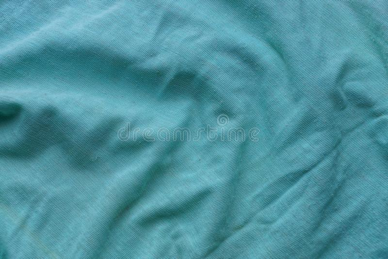 Green fabric texture from a piece of crumpled clothes. Green background of fabric from a piece of crumpled clothes stock photography