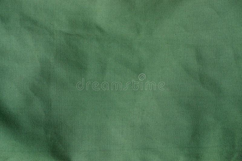 Green fabric texture from a piece of crumpled matter on clothes. Green background of fabric from a piece of crumpled matter on clothes royalty free stock photography