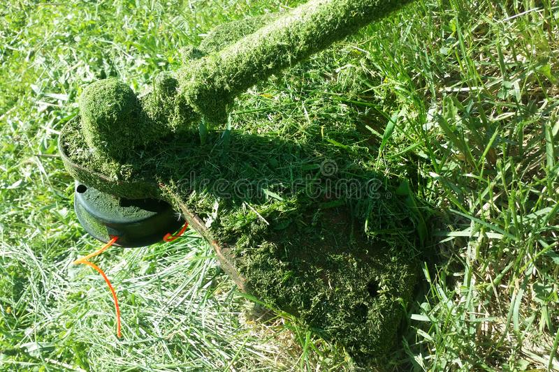 Green background with gasoline lawn mower with orange fishing line royalty free stock photos