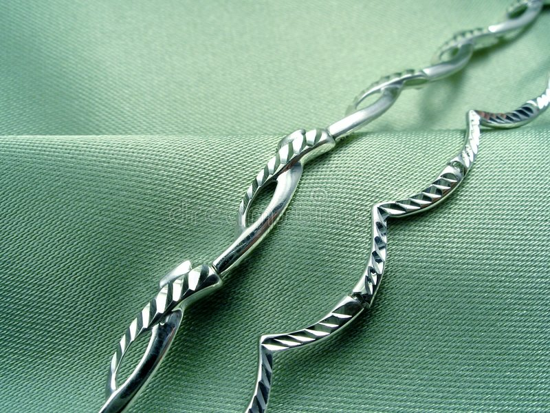 Green background with jewelry. Background with jewelry. Two bracelets on green textile royalty free stock photos
