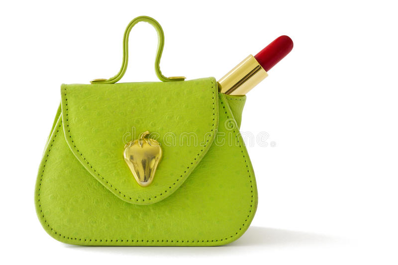 Green bag and red lipstick. Small green bag and red lipstick, isolated on white background stock photography