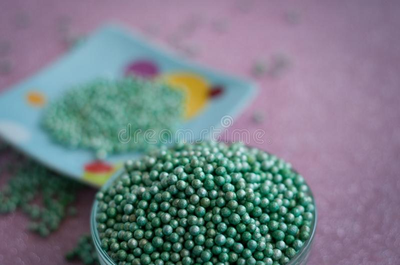 Green ball crystal sugar sprinkle dots, on glitter pink background. stock photos