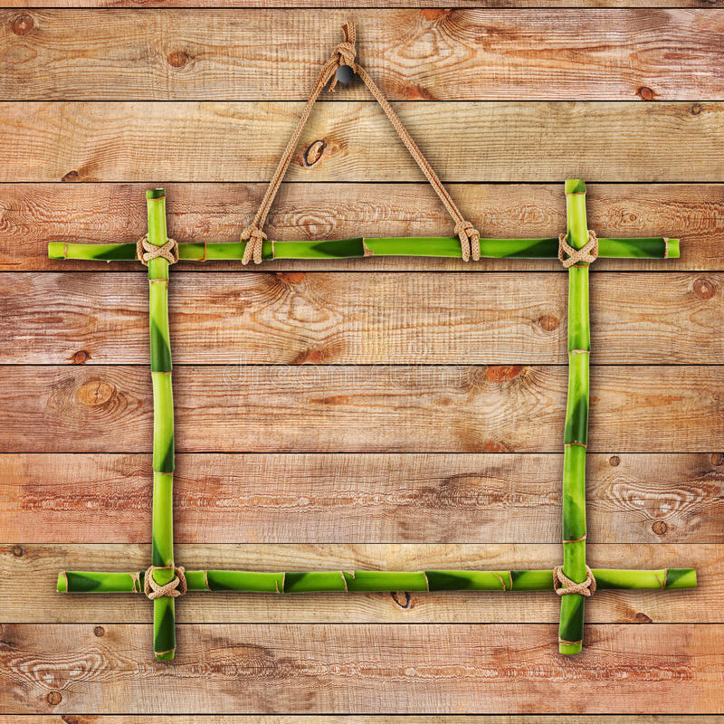 Green bamboo frame on natural wooden surface. royalty free stock photo