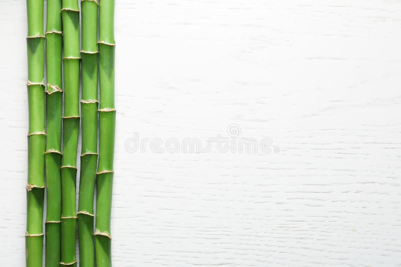 Green bamboo stems and space for text on wooden background. Top view stock photos