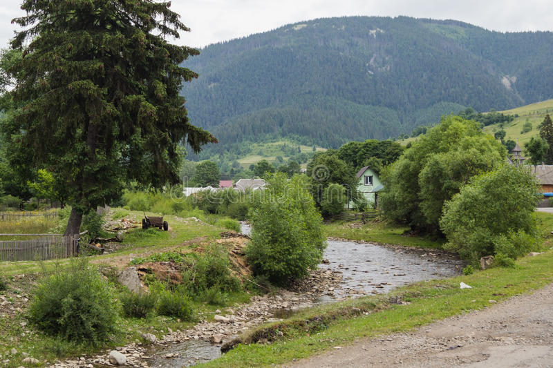 Green banks of river in mountain villlage. During summer stock photography
