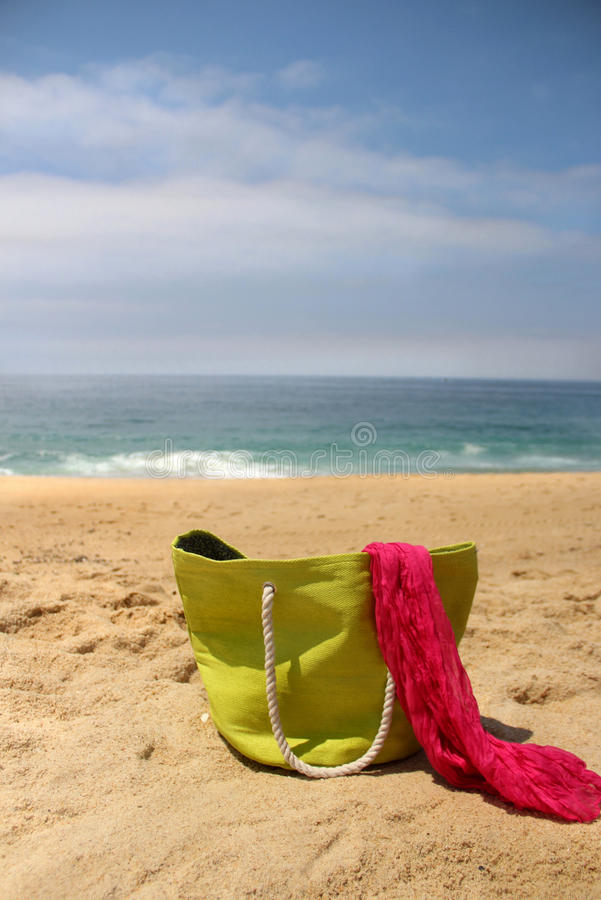 Green beach bag on the seacoast and pink shawl stock photos
