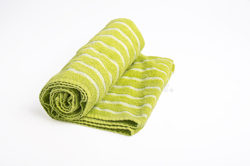 Green Beach Towel. A green beach towel, or bath towel rolled up - isolated on white stock images