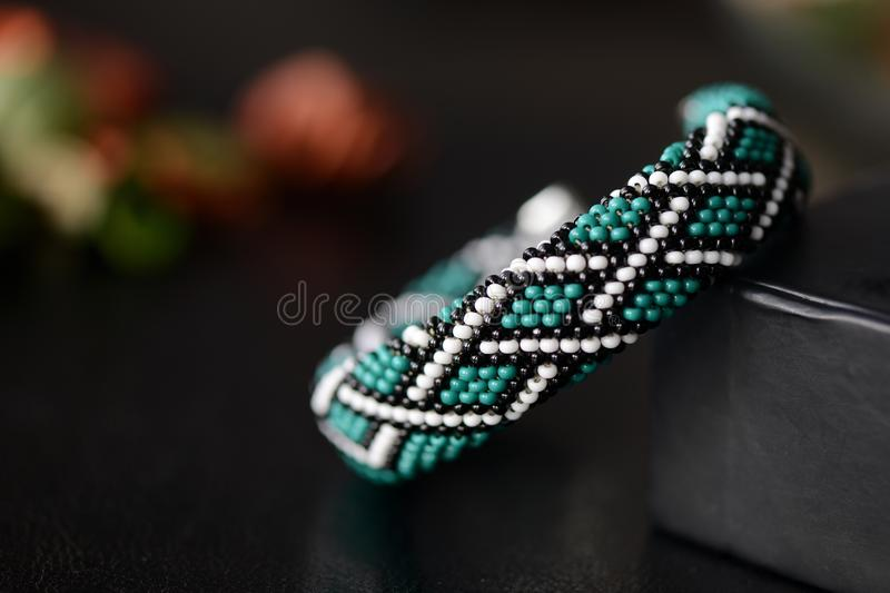 Green bead crochet bracelet with celtic print on a dark background stock photo