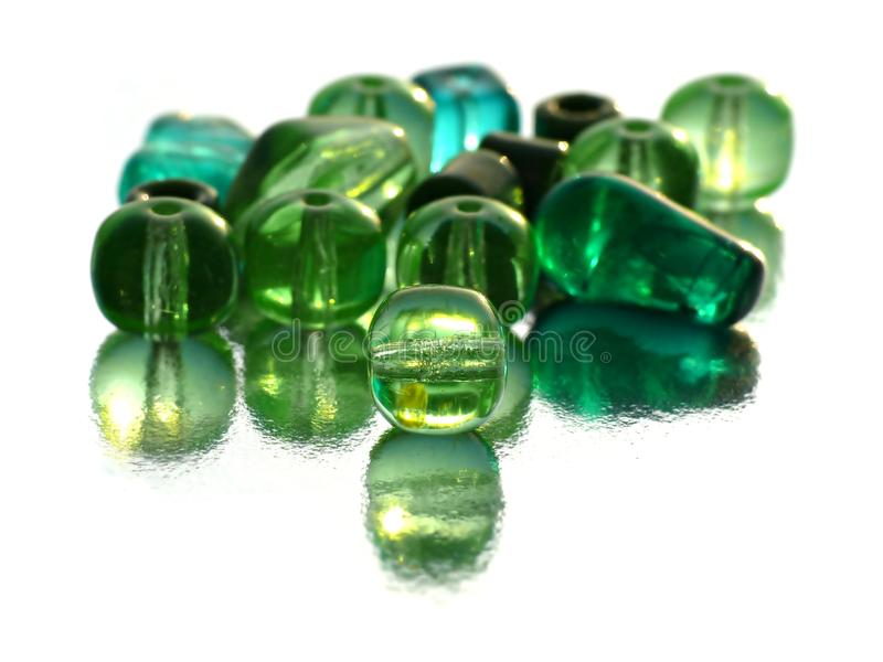 Green beads. With reflections on white stock image