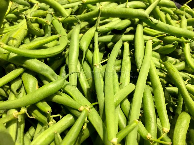 Green beans. Fresh green beans on display in the produce section of a grocery store stock image