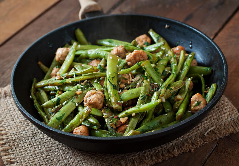 Green beans fried with chicken meatballs and garlic royalty free stock photo