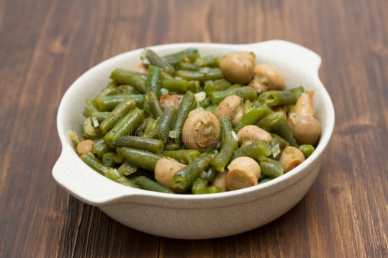 Green beans with mushrooms in dish on wooden background stock images