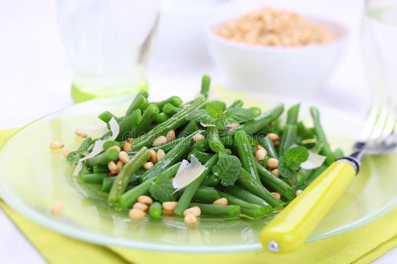 Green beans with pine nuts. Green beans with parmesan and pine nuts stock photo