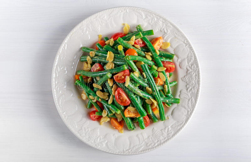 Green beans salad with bruschettas, Red, Yellow Tomatoes and flaked almond on white plate royalty free stock images