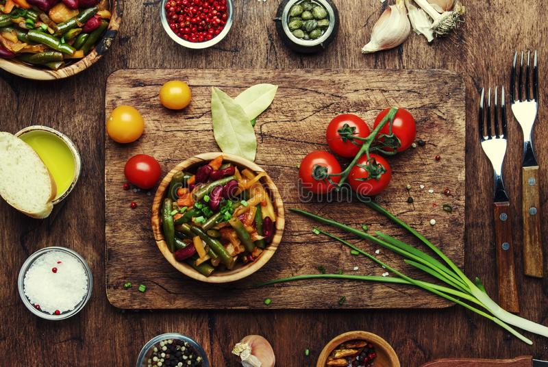Green beans with vegetables, mushrooms and tomatoes. Food cooking background, vintage wooden rustic table. Copy space, top view royalty free stock photos