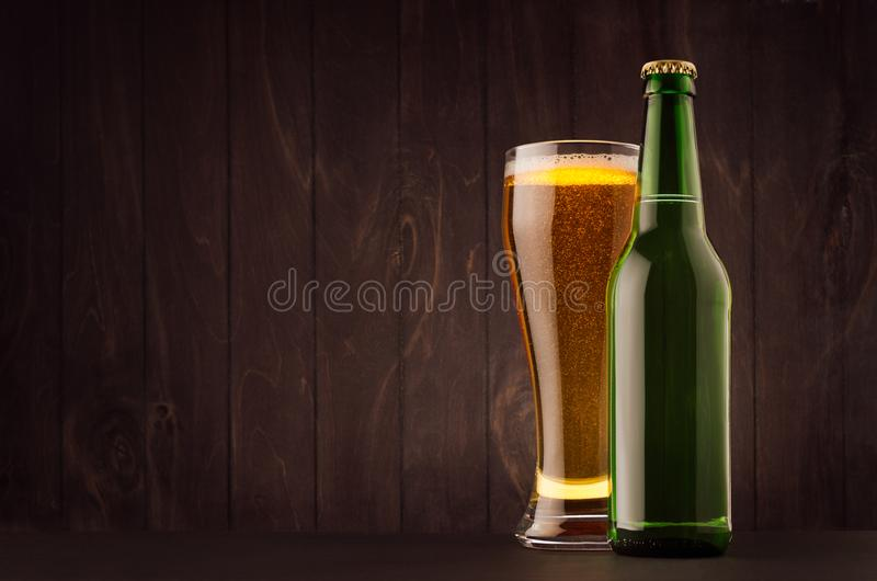 Green beer bottle and glass weizen with golden lager on dark brown wood board, copy space, mock up. Template for advertising, design, branding identity stock image