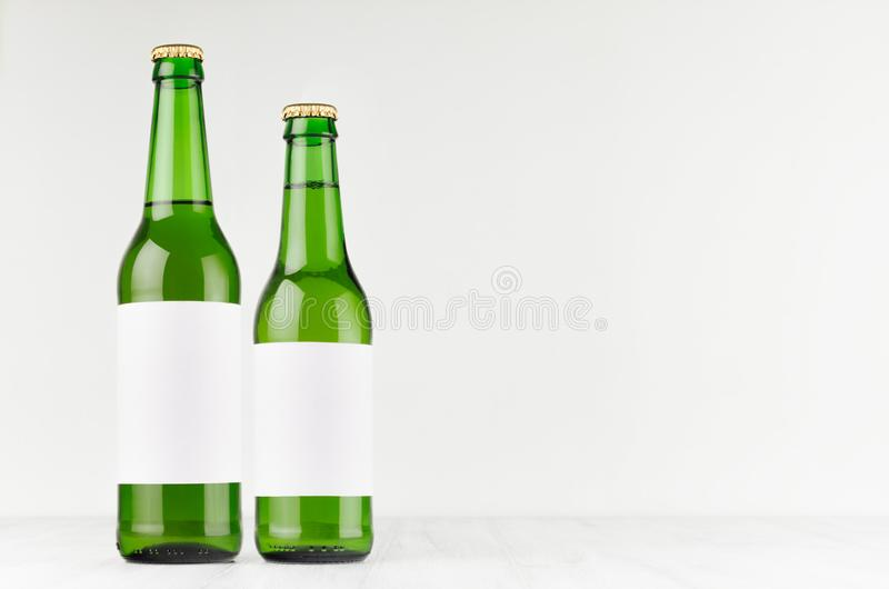 Green beer bottles longneck 500ml and 330ml with blank white label on white wooden board, mock up. royalty free stock images
