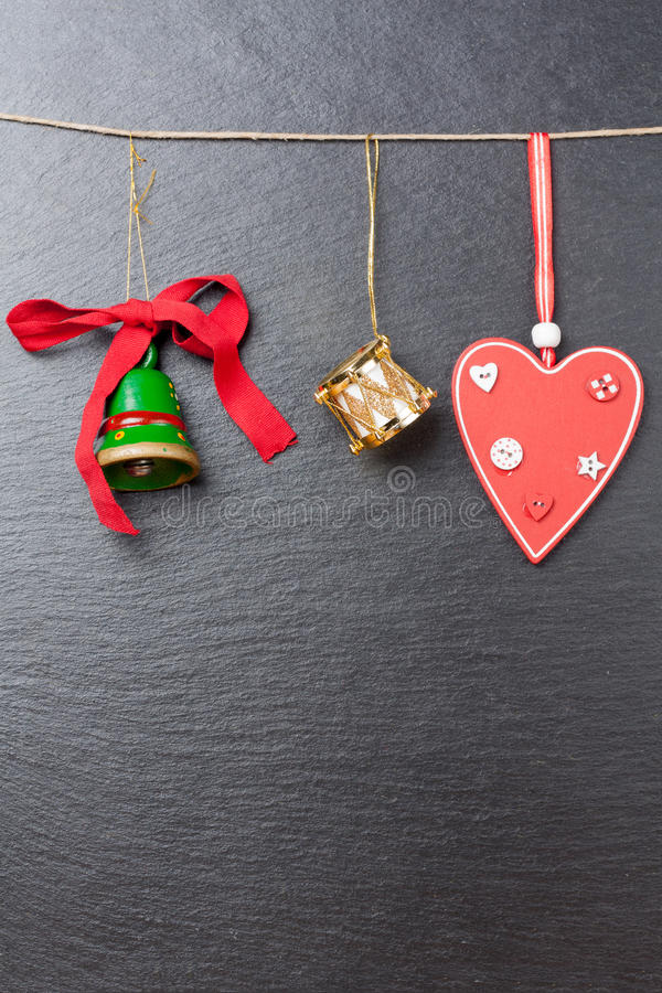 Green bell, golden drum and red heart. Christmas ornament: green bell, golden drum and red heart with a slate stone as background royalty free stock images