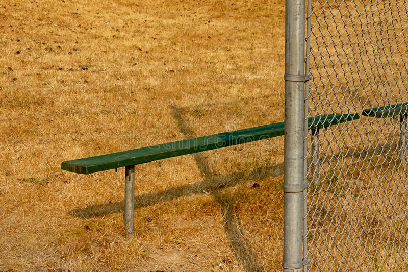 Green bench on edge of summer ball field. With silver chain link fencing royalty free stock photo
