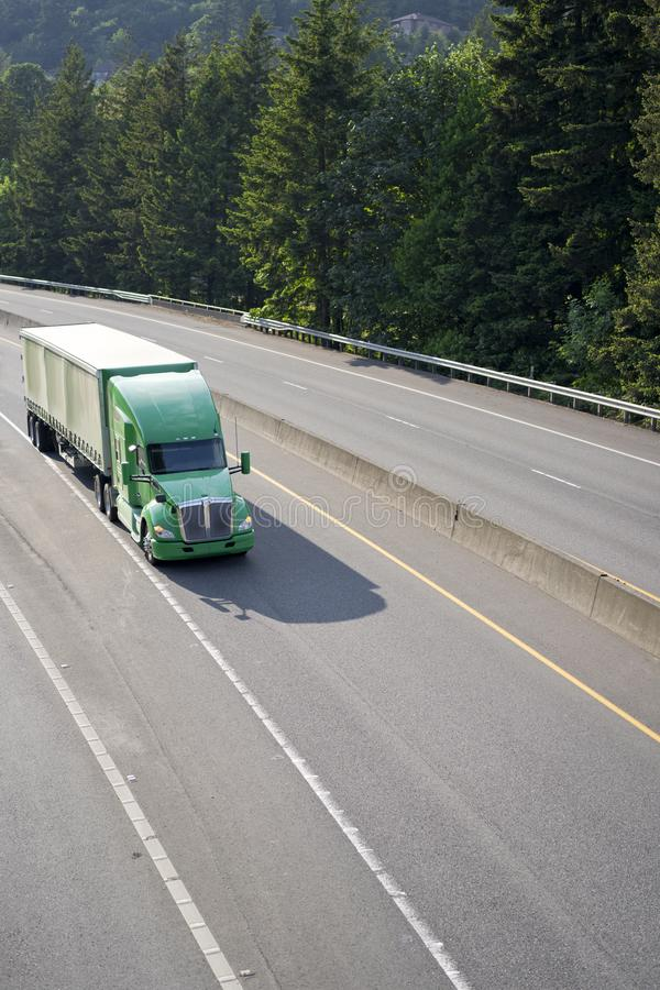 Green big rig American semi truck with tented semi trailer moving on wide divided highway with trees on background. Green big rig American long haul semi truck stock photography