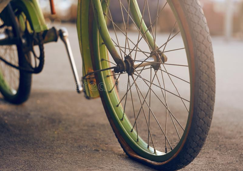 The green bike, standing on the asphalt with a flat tire. Beautiful retro bike green, standing on the asphalt with a flat tire on the wheel and illuminated by stock images