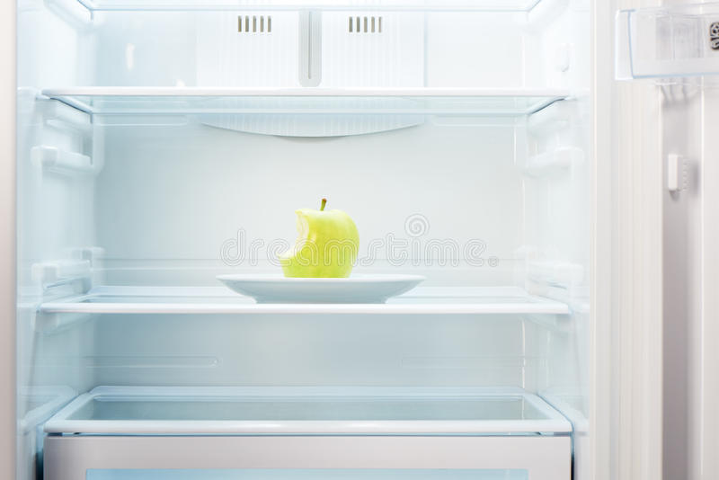 Green bitten apple on white plate in open empty refrigerator stock image