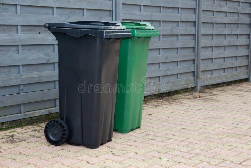 Green black grey recycle bins align a neighborhood street. A Green black grey recycle bins align a neighborhood street royalty free stock image