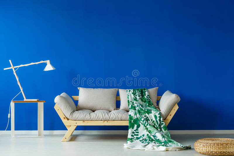 Green blanket lying on sofa. Green patterned blanket lying on a cozy, scnadi style sofa stock photos