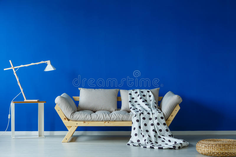 Green blanket lying on sofa. Green patterned blanket lying on a cozy, scnadi style sofa stock photography