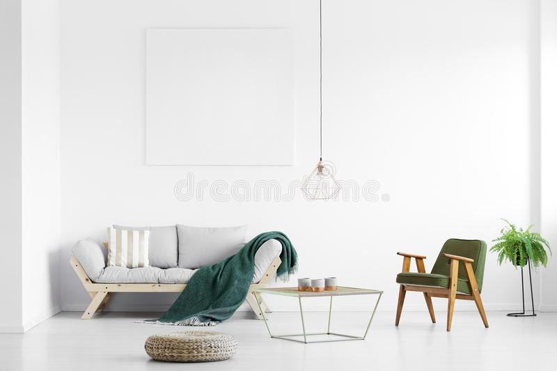 Green blanket on sofa. Dark green blanket thrown on grey sofa in bright living room with empty poster and armchair stock images